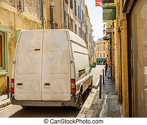 Dirty delivery van on narrow city street