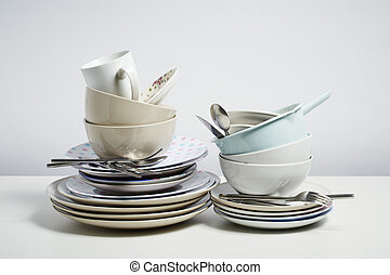 Dirty dishes pile needing washing up on white background