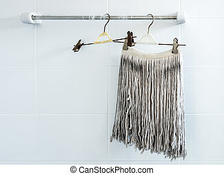 Dirty fabric mopped is  hanging in the bathroom.