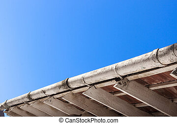 Dirty Gutter and Roof Trusses against blue sky - Underview ...