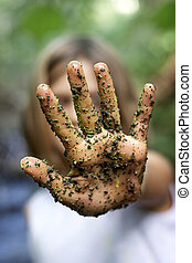 A childs hand with paint and grains of sand and dirt, in the stop position, focus on the hand, very shallow depth of field