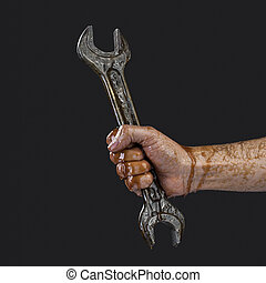 dirty hand holding tool, spanner