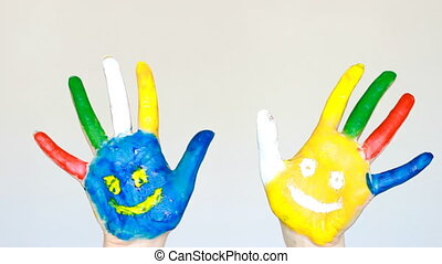Dirty hands painted different colors with smiles. The concept of happiness, good mood, joy, creativity, art and painting