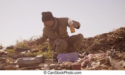 dirty homeless hungry man in a dump drinks the missing juice...