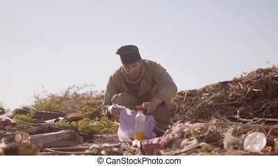 dirty homeless hungry man in a dump eating orange for food in lifestyle the package with walking goes looking for food slow motion video. homeless dirty man roofless person looking for food in a dump. refugee homeless illegal immigration poverty concept