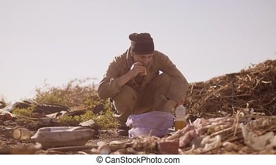 dirty homeless hungry man in a dump eating orange for food...