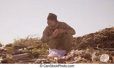 dirty homeless hungry man in a dump eating orange for...