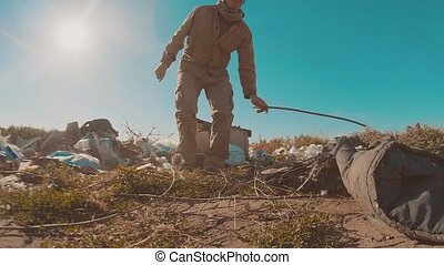 dirty homeless lifestyle man at the dump slow motion video. homeless roofless person looking for food in a dump. refugee homeless illegal immigration poverty concept