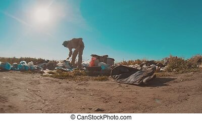 dirty homeless man at the dump slow motion video. homeless roofless person looking for food in a dump lifestyle. refugee homeless illegal immigration poverty concept