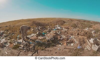 dirty lifestyle homeless man at the dump slow motion video. homeless roofless person looking for food in a dump. refugee homeless illegal immigration poverty concept