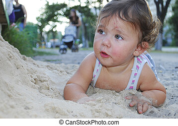 Dirty little girl lying in the sand near the playground.