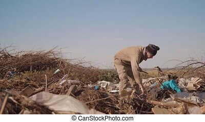 dirty male homeless hungry man in a dump drinks looking for...