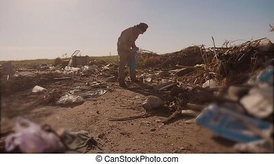 dirty male homeless hungry man in a dump looking for...