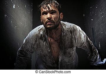 Dirty man between grunge walls