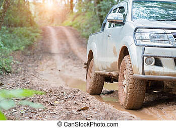 Dirty offroad car, SUV covered with mud on countryside road, Off-road tires, offroad travel and driving concept.