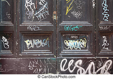 dirty, old, black, wooden doors, many white graffiti on...