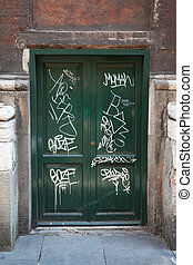 dirty, old, green, wooden doors, many white graffiti on...