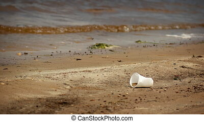 Dirty plastic cup on the shore of the pond. Garbage concept
