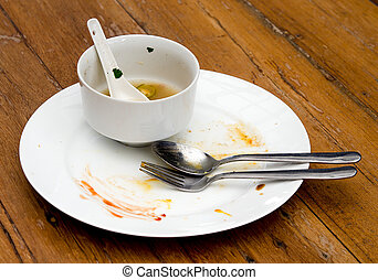 Dirty plate with spoon  and fork on wood table