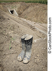 Dirty protective boots at irrigation channel construction site