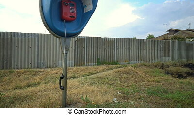 Dirty public telephone with a dropped receiver swaying in...