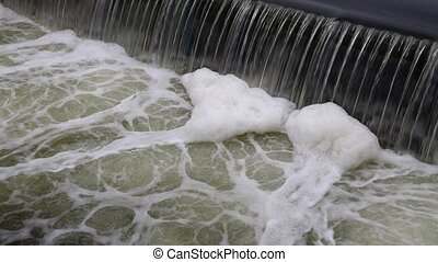 Dirty river water falling from rift and foam - Dirty...