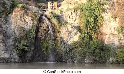 Waterfall of sewage rushes down from a pipe in mountain river, amid picturesque landscape. Seagulls.