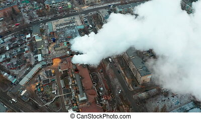 White thick smoke from factory pipes pollutes the city's air - an industrial impact on global warming and the planet's climate. Dangerous emissions of pollutants into the atmosphere.
