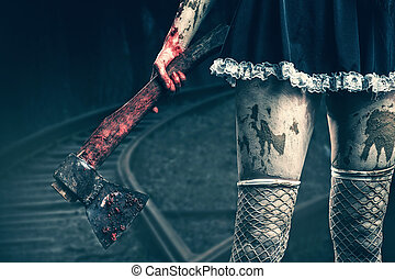 Dirty woman's hand holding a bloody axe