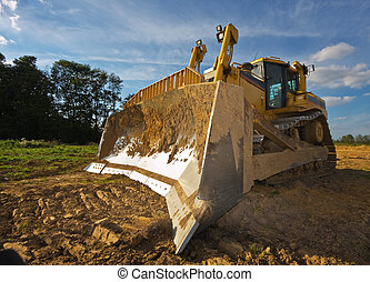 Dirty yellow bulldozer photographed in a sunny summer day