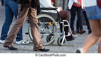 Close up of woman on a wheelchair with a helper during walk in the busy street.