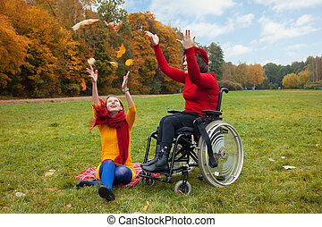 disabled with a friend walking in the autumn Park
