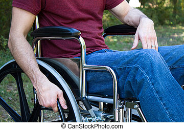 Man disabled by an accident sits in a wheelchair outside.