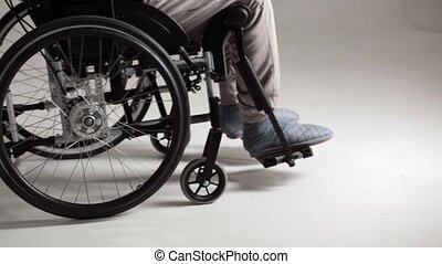 Disable man in casual clothes in a wheelchair. Studio shot