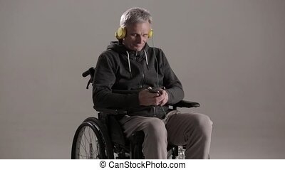 Disable man in casual clothes in a wheelchair. Studio shot -...