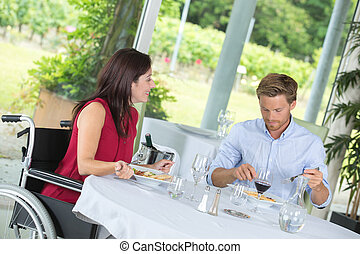 disable woman having dinner in a restaurant with her husband