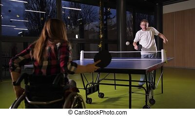 Disabled adult people playing table tennis