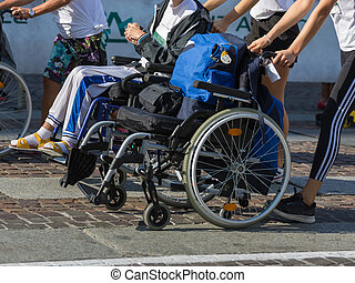 Disabled Athlete in a Sport Wheelchair during Marathon Helped by Female Runners