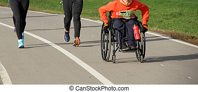 Disabled athletes in a wheelchair participate in a running competition