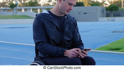 Young disabled athletic using mobile phone at sports venue 4k