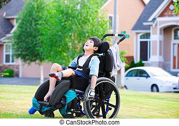 Disabled boy in wheelchair enjoying time at the park