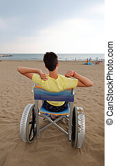 disabled boy in a wheelchair lokks at the sea