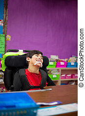 Disabled seven year old boy sitting at desk in classroom