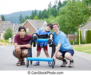 Disabled boy in walker surrounded by father and older brother