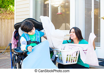 Disabled boy in wheelchair helping teen sister fold laundry...