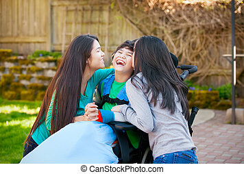 Disabled boy in wheelchair laughing with teen sister on...