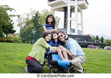 Disabled boy in wheelchair surrounded by family