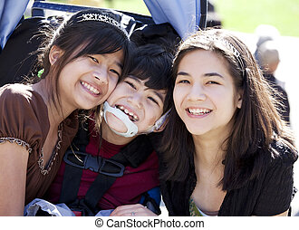 Disabled boy in wheelchair surrounded by big sisters, smiling
