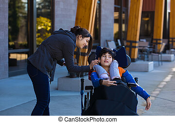 Disabled boy in wheelchair using earbuds with caregiver