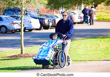 Disabled boy in wheelchair walking at park with father